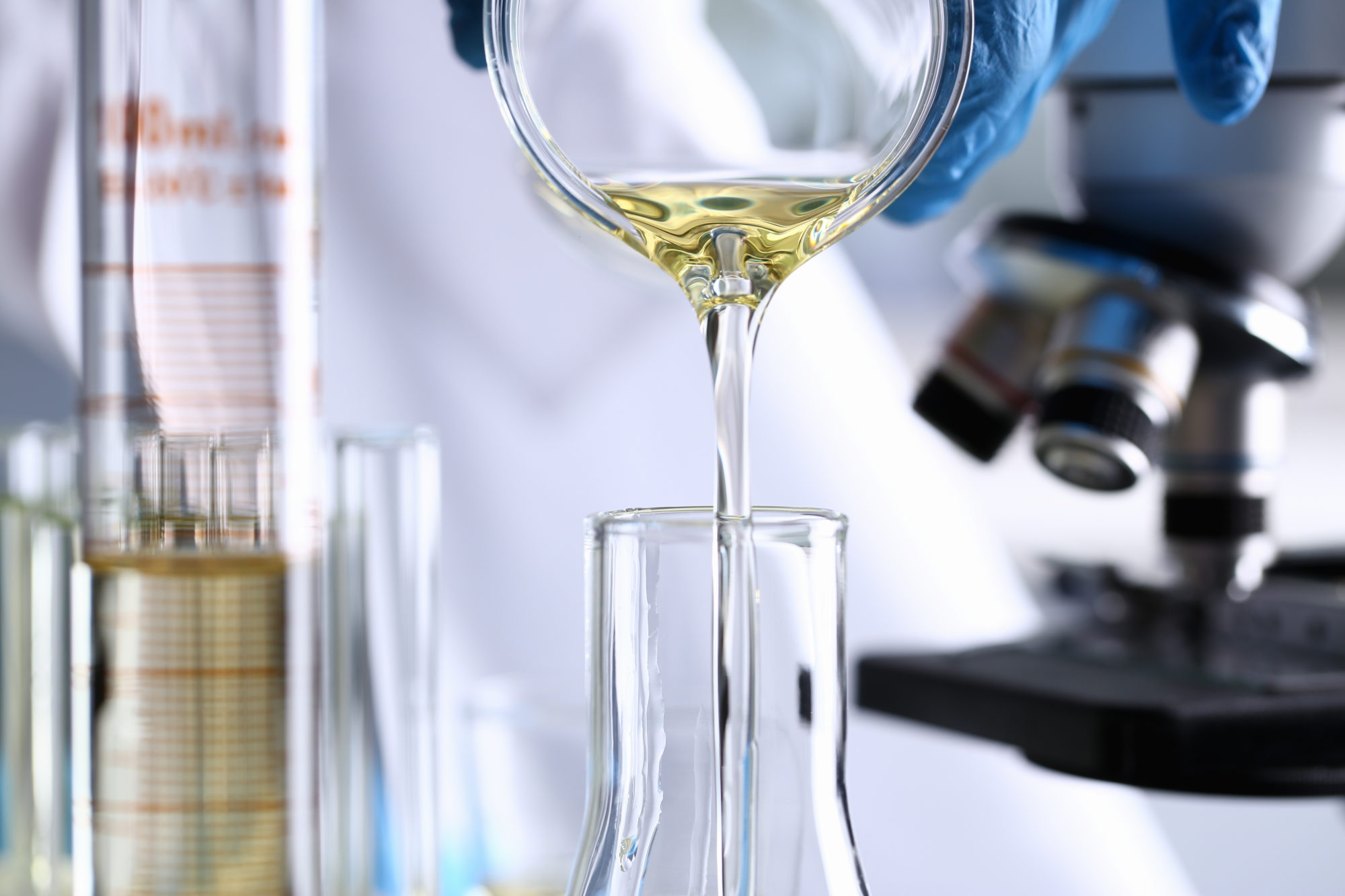 Male hand hold yellow liquid in test tube. Conveyor line production household cleaning products detergents help cleaning destruction stains pests urine poison antidote vaccine concept.